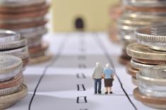 Couple de retraités empruntant une route avec des pièces de monnaie de chaque côté