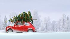 Sapin de Noël décoré sur le toit d'une voiture rouge par temps neigeux