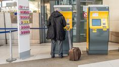 Voyageur devant dans une gare SNCF qui achète son billet