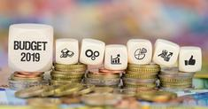 Un gros cube Budget 2019 ainsi que 6 autres cubes représentant des symboles sur le thème de l'argent et pièces de monnaie empilées sous les 7 cubes
