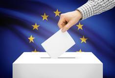 Main déposant dans une urne un bulletin de vote pour les élections européennes (drapeau européen représenté)