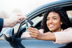 Jeune fille au volant de sa voiture lors de la remise des clés